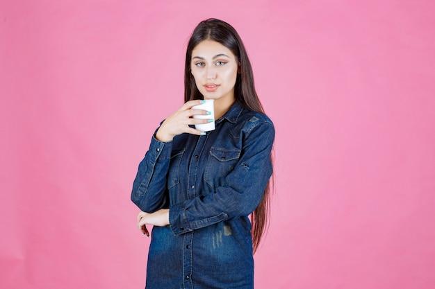Chica en camisa vaquera disfrutando de una taza de café desechable