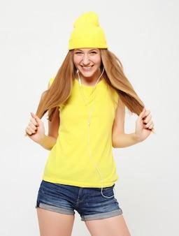 Chica en camiseta amarilla bailando con expresión de la cara inspirada.