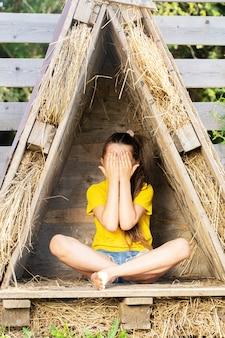 Chica en una camiseta amarilla brillante se esconde en una pequeña cabaña