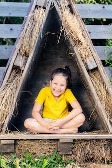 Chica con una camiseta amarilla brillante se sienta en una pequeña cabaña