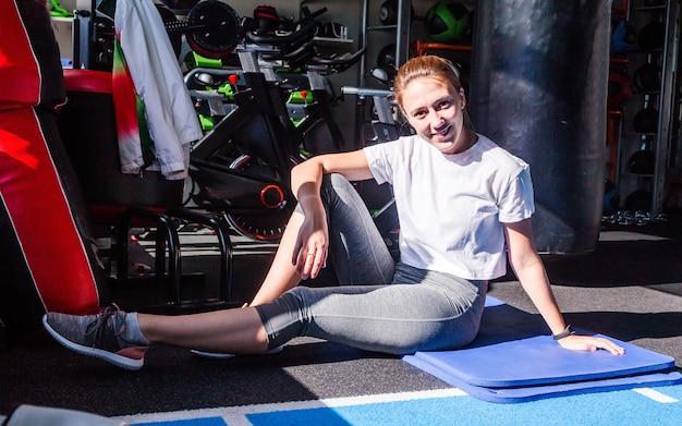 Una chica con una camiseta blanca y mallas grises se sienta en una colchoneta de gimnasia en un gimnasio, sonríe y mira a la cámara. luz solar y sombras duras en un gimnasio.