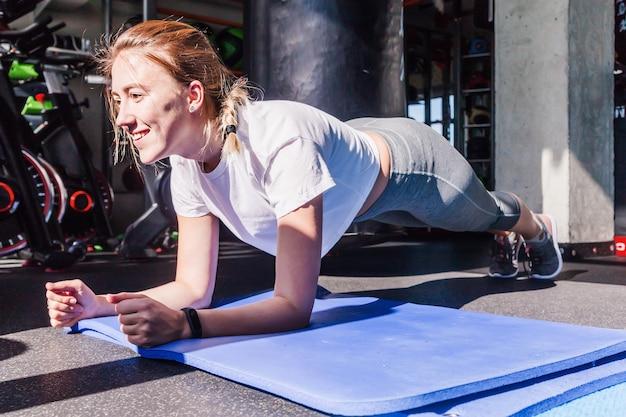 Una chica con una camiseta blanca y mallas grises se sienta haciendo la barra sobre una colchoneta de gimnasia en un gimnasio. luz solar y sombras duras en un gimnasio. foto horizontal