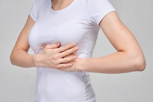 Una chica con una camiseta blanca se masajea el pecho. problemas de mamas.