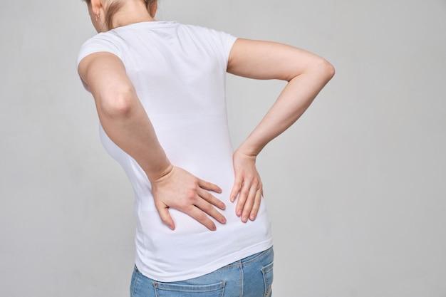 Una chica con una camiseta blanca se masajea la zona lumbar por un dolor intenso. ciática, sciosis.