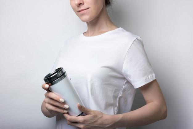 Chica con una camiseta blanca sostiene una termocup con café. en blanco para la marca. maqueta monocromo