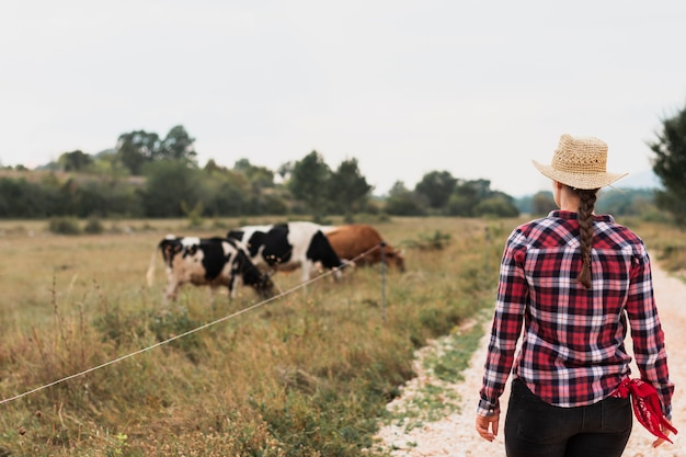 Chica en camiseta cuadrada roja viendo vacas pastando