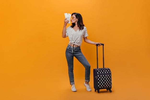 Chica en camiseta de lunares besa boletos y sostiene la maleta sobre fondo naranja