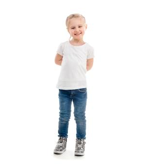 Chica en camiseta de pie aislado sobre fondo blanco.