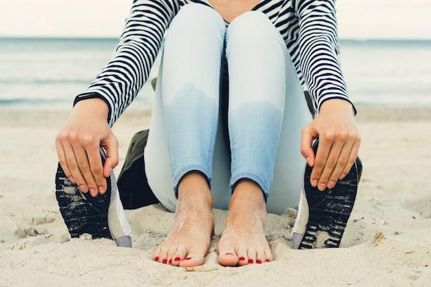 Chica en camiseta a rayas y jeans se sienta descalza en la playa al lado de los zapatos