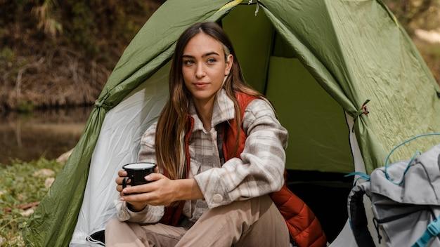 Chica de camping en el bosque sosteniendo una taza