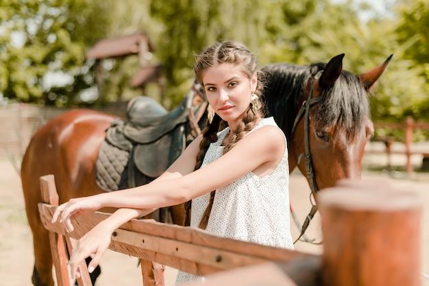 Chica de campo en un pueblo con un caballo sobre un fondo