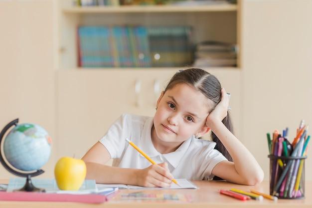 Chica cansada sentado en el escritorio de la escuela
