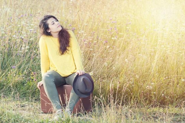 Chica cansada con sombrero sentado y descansando sobre la maleta vintage marrón en el camino del campo durante el atardecer de verano