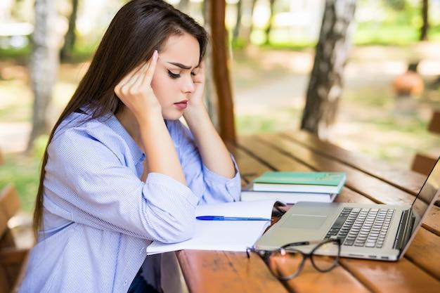 Chica cansada usando una computadora portátil en una mesa del parque al final del día