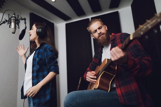 La chica canta, y el chico toca la guitarra.