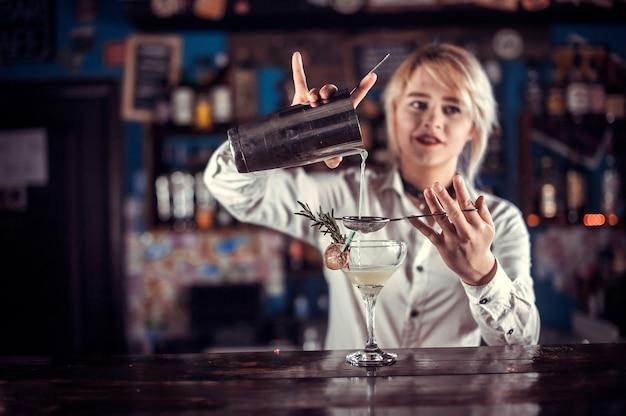 Chica carismática barman demuestra el proceso de hacer un cóctel mientras está de pie cerca de la barra del bar en el pub