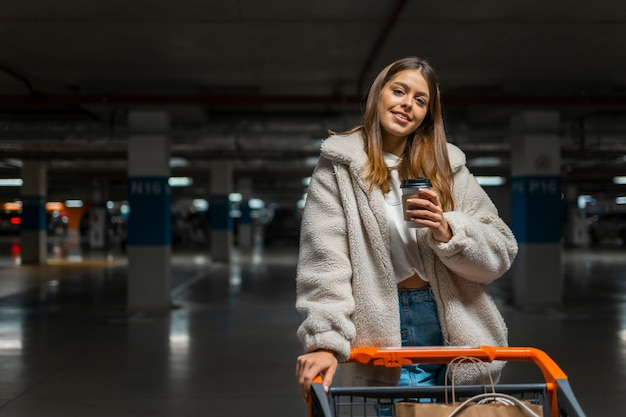Chica con carrito de compras en el aparcamiento subterráneo