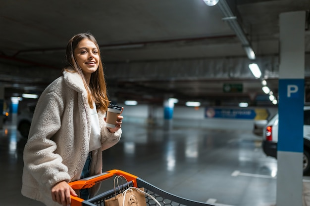 Chica con carrito de compras en el centro comercial