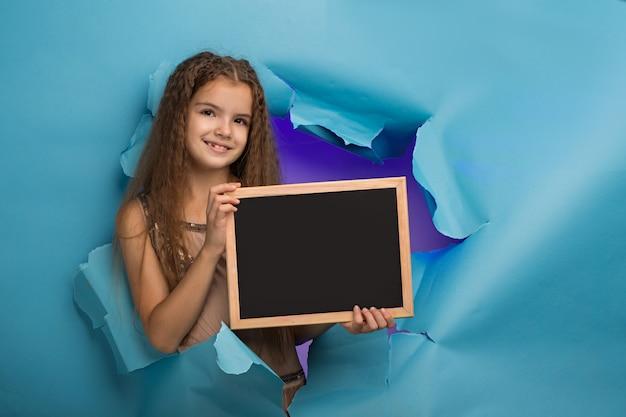 Chica con un cartel se asoma por un agujero en papel azul