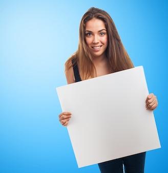 Chica con un cartel en un fondo azul