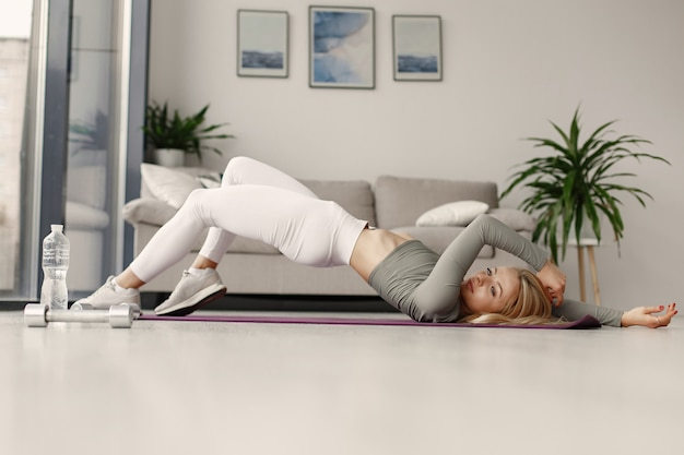 Chica en casa. mujer hacer yoga. señora con mancuernas y agua.
