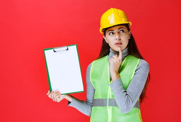 Chica de casco amarillo sosteniendo una carpeta de proyecto y pensando.
