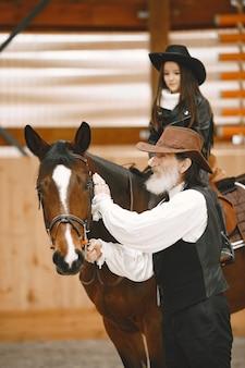 Chica en casco aprendiendo a montar a caballo. el instructor enseña a la niña. Foto Premium