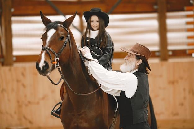 Chica en casco aprendiendo a montar a caballo. el instructor enseña a la niña.