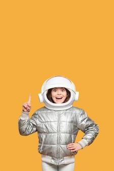 Chica con casco espacial señalando