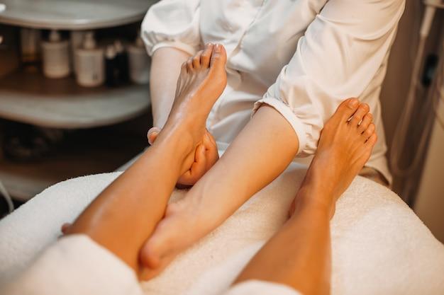 Chica caucásica acostada mientras un médico está enviando mensajes a sus piernas en un salón de spa