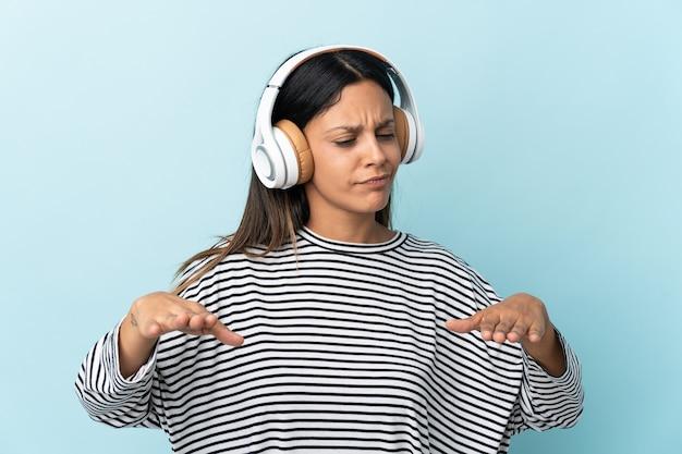 Chica caucásica aislada en la pared azul escuchando música y bailando
