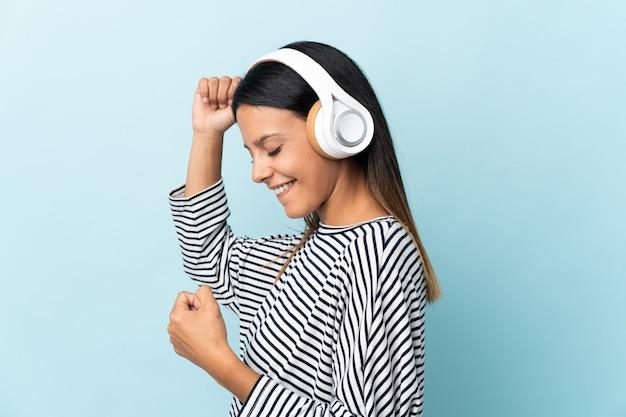 Chica caucásica aislada sobre fondo azul escuchando música y bailando