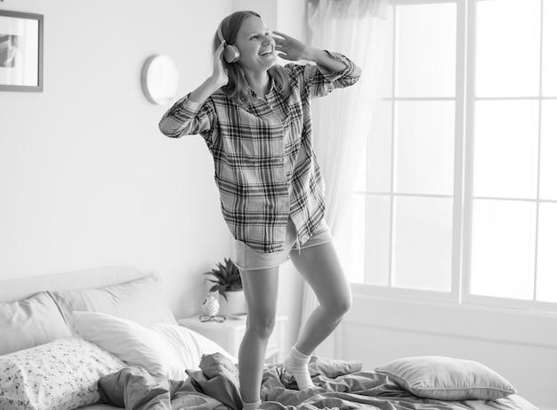 Chica caucásica bailando en la cama