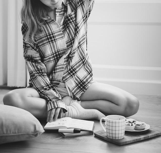 Chica caucásica estudiando en el piso