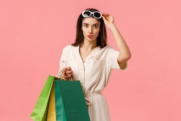 Chica caucásica femenina glamour divirtiéndose relajante, sosteniendo bolsas de compras y labios plegables