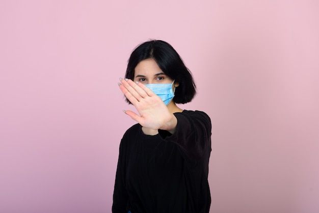 La chica caucásica en mascarilla protectora de color azul. la mujer. retrato de disparo. concepto de protección contra virus y contaminación.