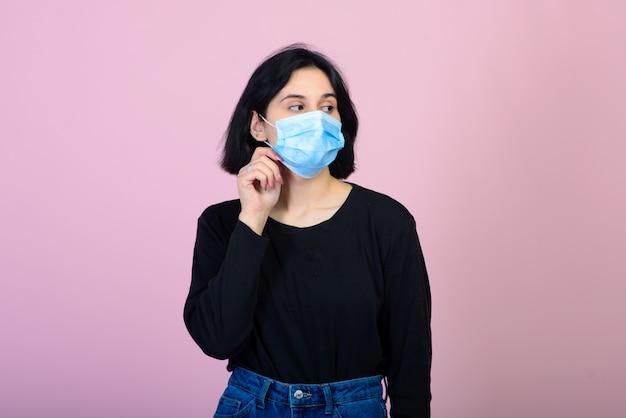 La chica caucásica en mascarilla protectora de color azul.