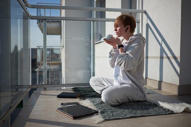 Chica caucásica pelirroja sentada en cuadros en el balcón con tableta en la mañana y disfrutando de un café recién hecho