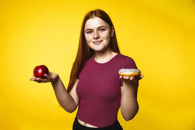 La chica caucásica pelirroja sonrió sostiene la manzana en una mano y la rosquilla en la otra