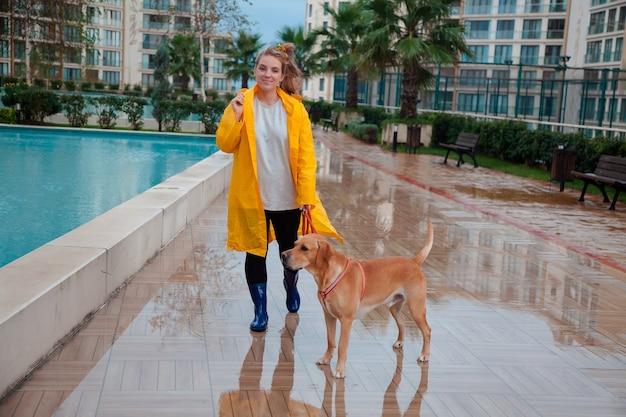 Chica caucásica con un perro caminando afuera en el día lluvioso de otoño.