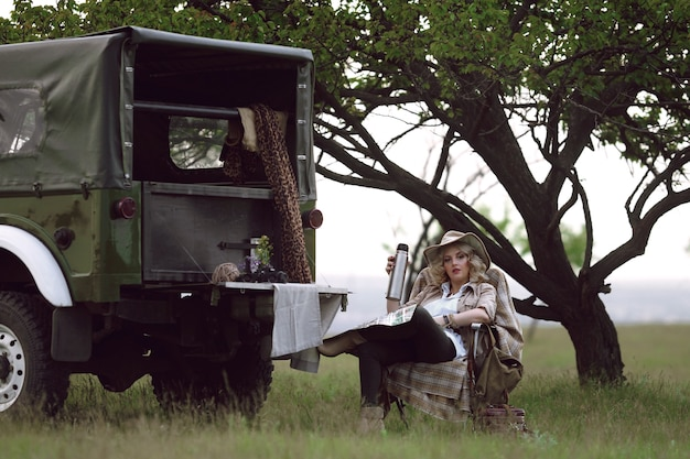 Chica cazadora cerca de coche safari con té