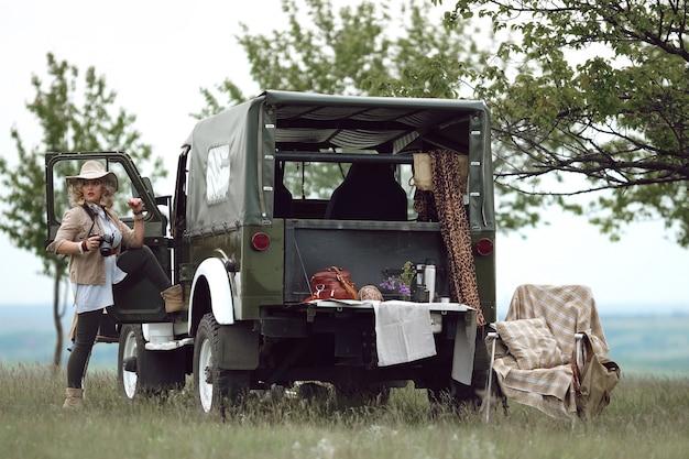 Chica cazadora cerca de coche safari