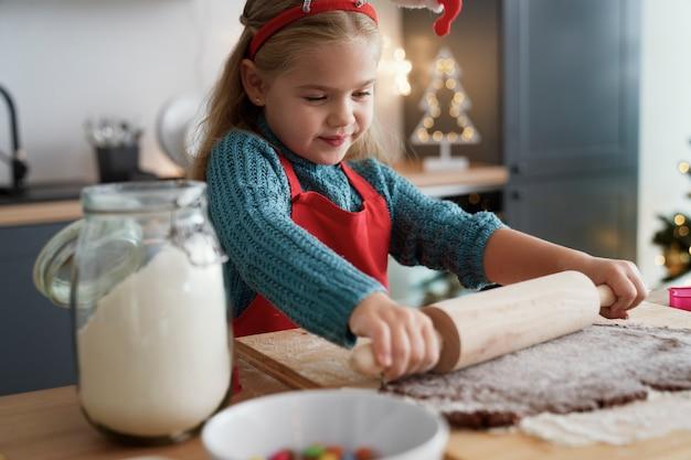 Chica se centra en rodar la masa de pan de jengibre