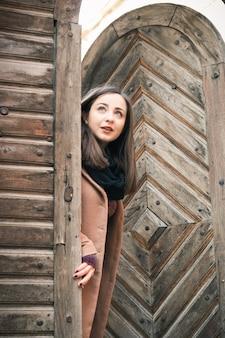 Chica cerca de la antigua puerta de madera