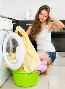 Chica cerca de la lavadora