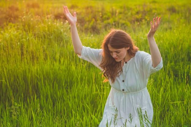 Chica cerró los ojos, rezando en un campo durante la hermosa puesta de sol