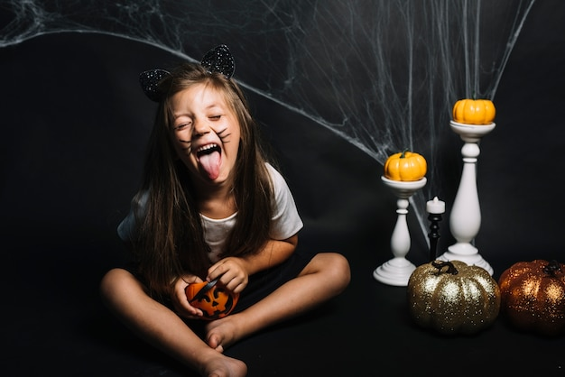 Chica con cesta de truco o trato cerca de decoraciones de halloween