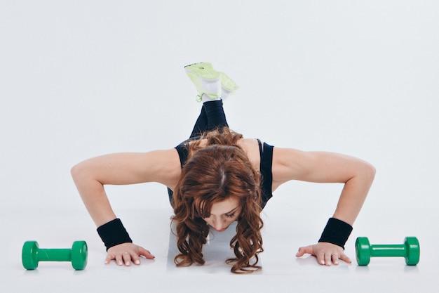 Chica en un chándal haciendo ejercicios con pesas. la mujer hace push-ups desde el piso. concepto de estilo de vida saludable, uniformes deportivos, copa del mundo, gimnasio, ropa especializada, uniformes negros.