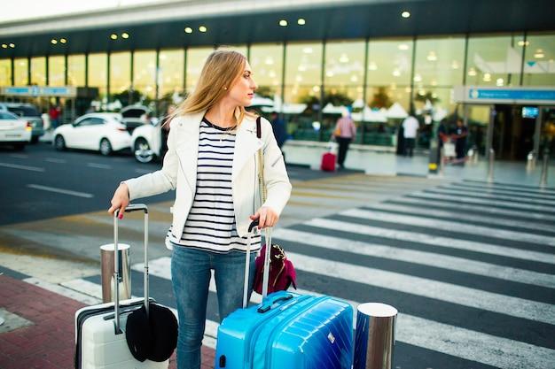 Chica en chaqueta blanca se encuentra en la travesía con maletas azul y blanco