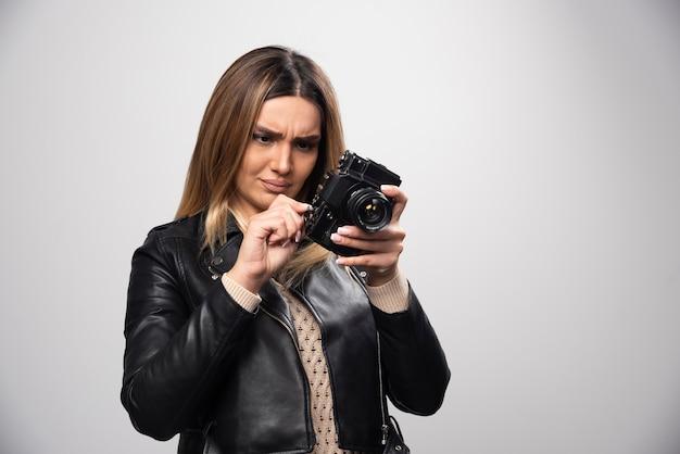 Chica con chaqueta de cuero comprobando el historial de fotos en la cámara y parece insatisfecha.